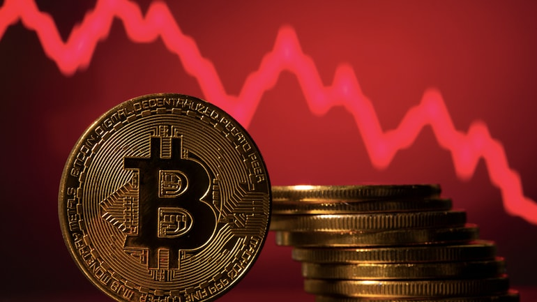 Bitcoins in front of a red downward chart