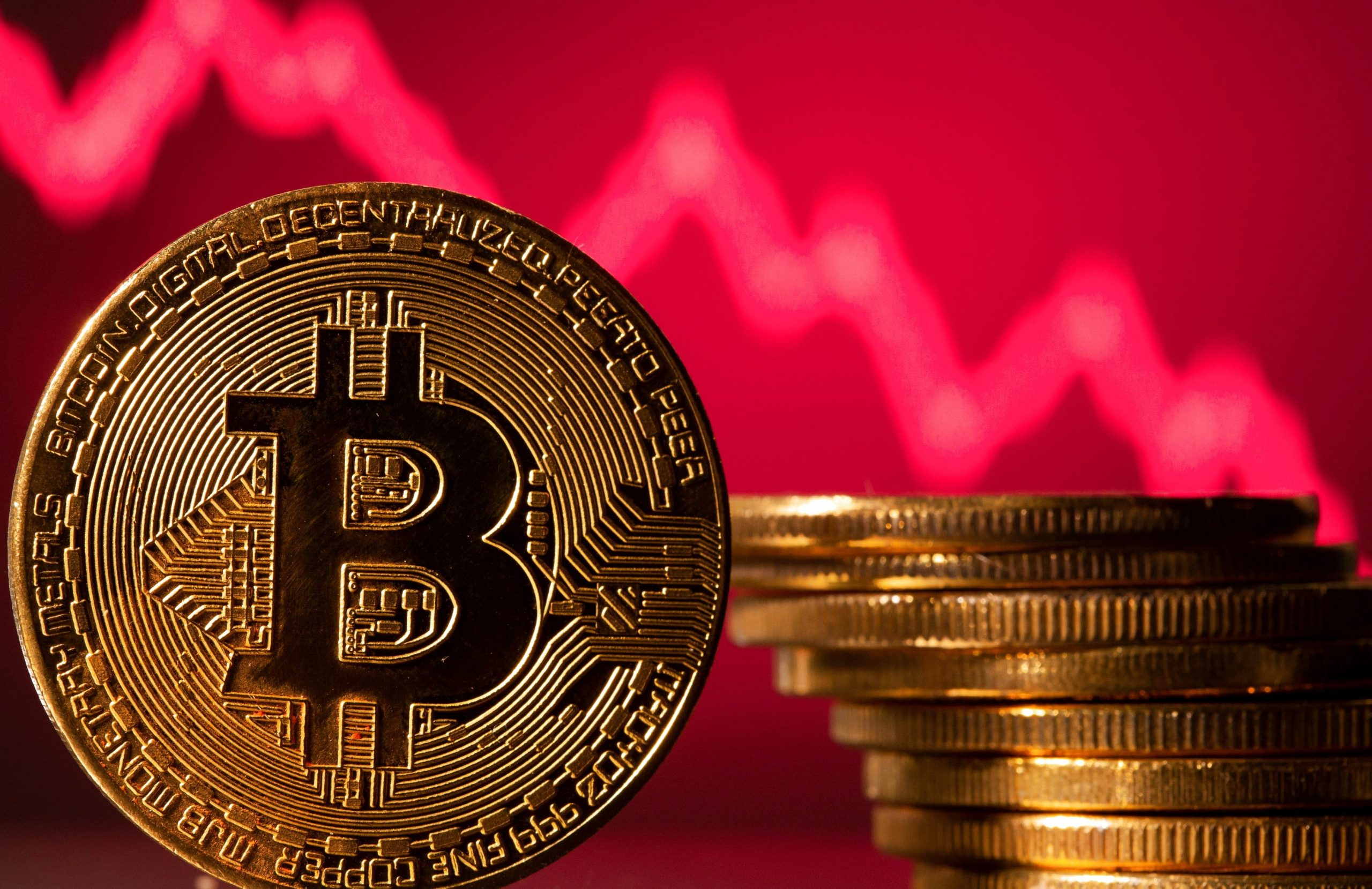 Picture of a standing bitcoin next to stacked bitcoins with a red downwards facing arrow behind them