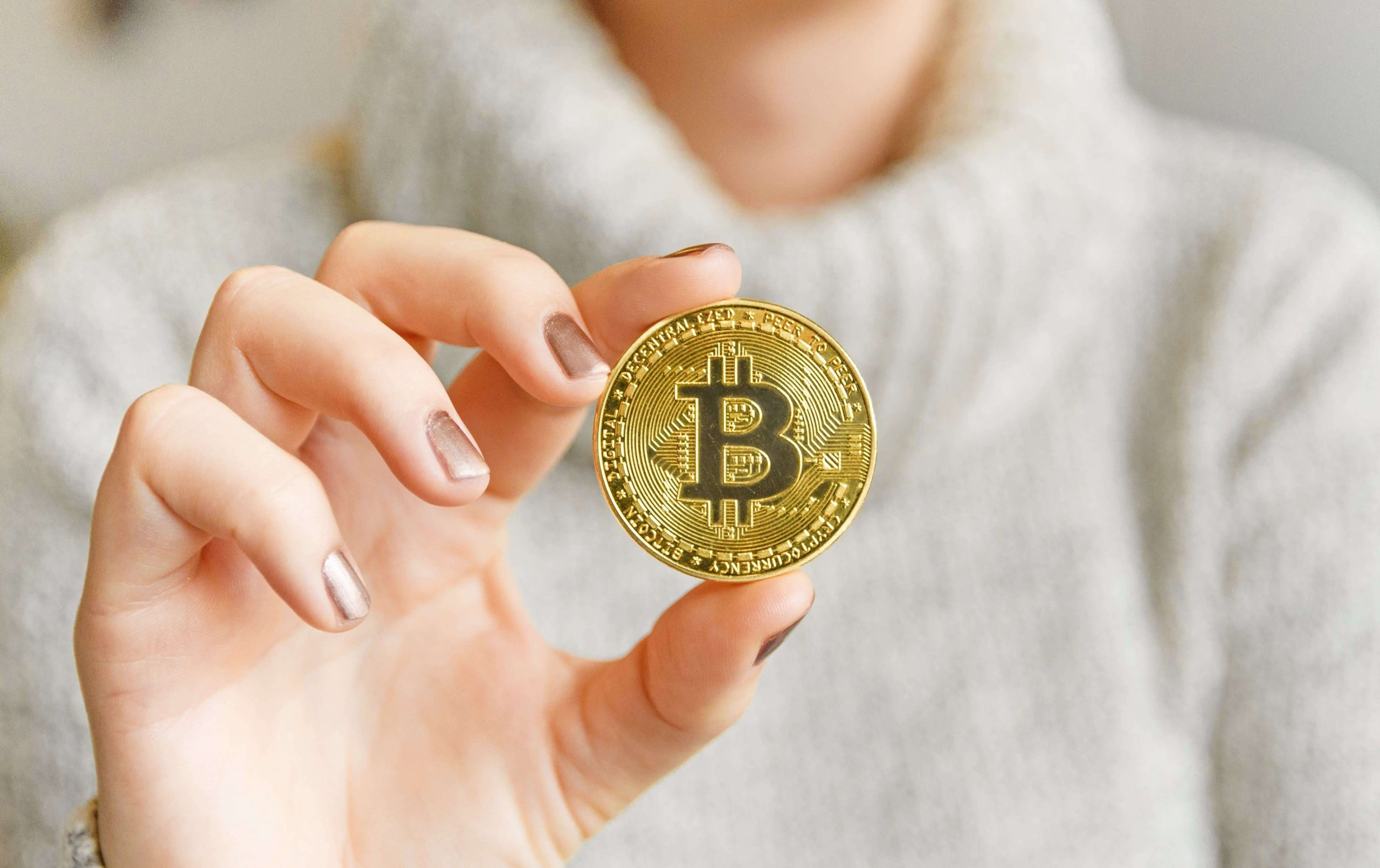 Picture of a hand holding a bitcoin