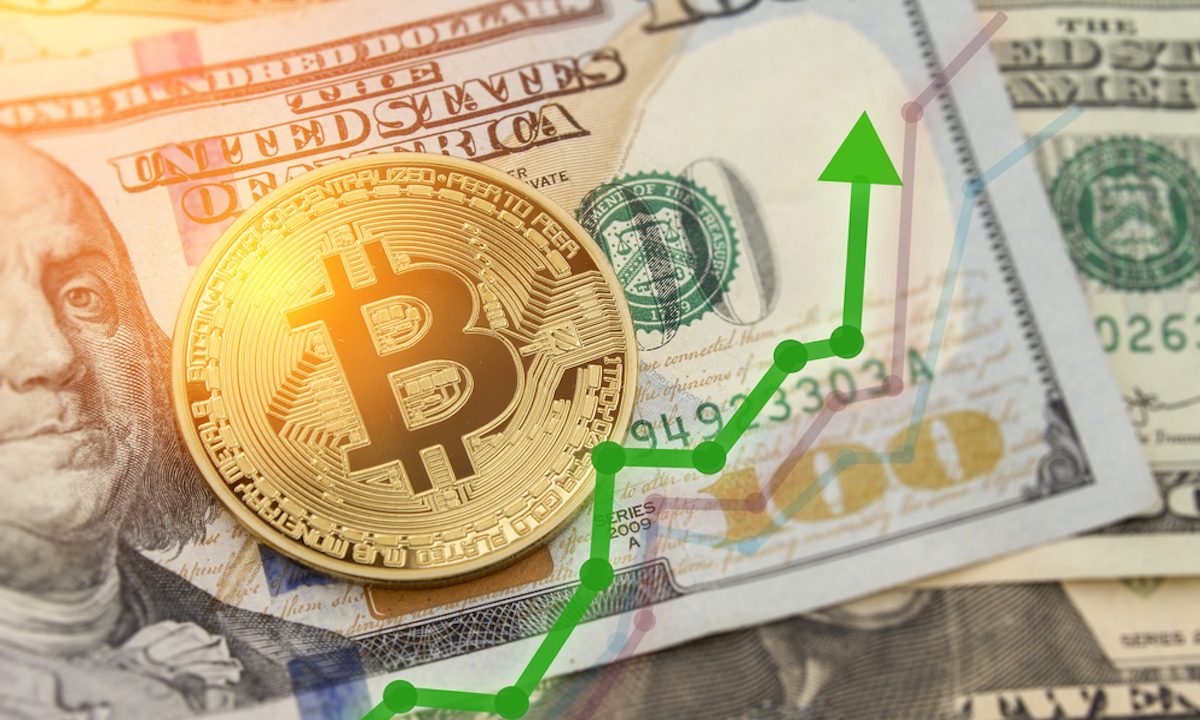 Picture of a bitcoin laying on a $100 bill, with a green upward arrow next to it