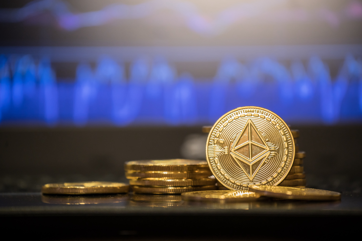 Picture of an ETH coin standing with other Ethereum coins laying around it