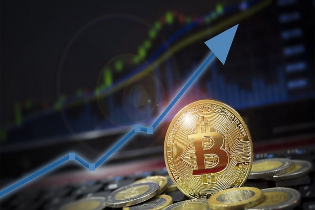 Picture of a gold bitcoin with a blue arrow pointing upwards behind it