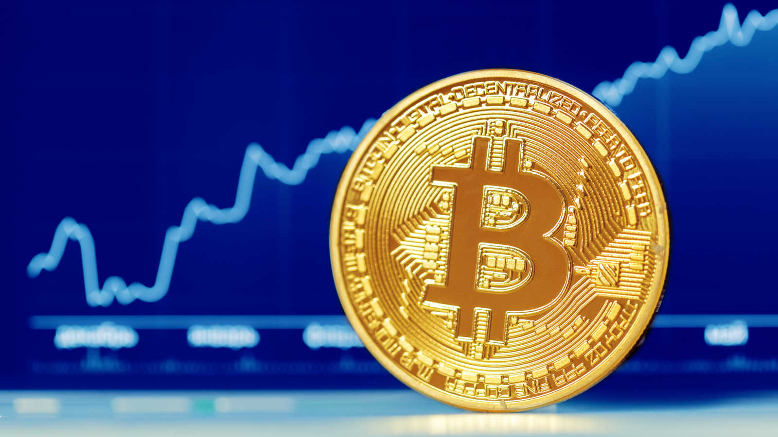 Picture of a bitcoin in front of a blue market chart